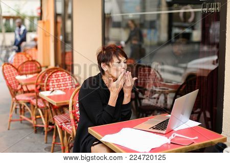 lady sitting in outdoor cafe and have conversation  with sister via laptop. Sisters not communicate for long time and woman very happy. Female smiling  waving,  blows air kiss and showing heart from hands. Concept of destruction of communication borders