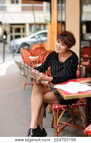 Woman sitting at table of street cafe skimmed through new newspaper. Female with short haircut dressed in black dress gestures  shares emotions with interlocutor. Lady smiling and looks wondering. Concept of involvement in news.