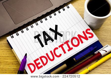 Tax Deductions. Business concept for Finance Incoming Tax Money Deduction written on notebook book on wooden background in the Office with laptop coffee