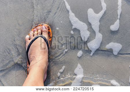 Leg of the male with wear flip flops while standing on the beach. The swash of seawater up the beach.