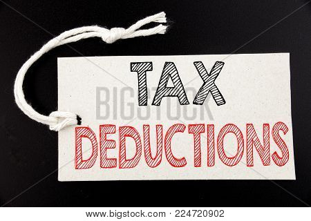 Handwritten text caption showing Tax Deductions. Business concept writing for Finance Incoming Tax Money Deduction written on price tag paper on black vintage background.