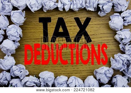 Handwriting Announcement text showing Tax Deductions. Business concept for Finance Incoming Tax Money Deduction written on wooden wood background with on old background with folded paper balls