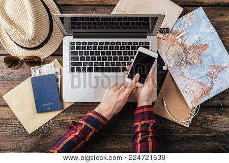 Booking tickets online. Female hands hold a smartphone. Planning a trip. Top view