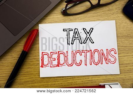 Handwriting Announcement text showing Tax Deductions. Business concept for Finance Incoming Tax Money Deduction written on paper, wooden background in office copy space, marker pen and glasses