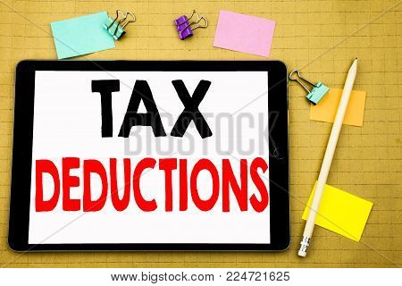 Hand writing text caption inspiration showing Tax Deductions. Business concept for Finance Incoming Tax Money Deduction Written on tablet, wooden background with sticky note and pen