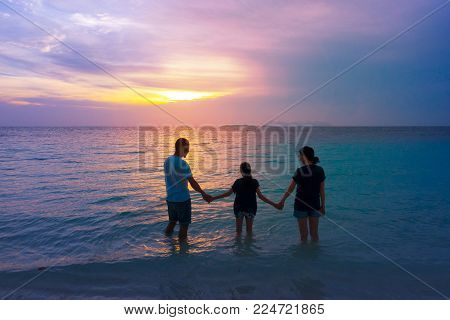 Happy Asian Family In Love On Vacation And Happy Valentines Day. Dad Mom And Daughter Holding Hands