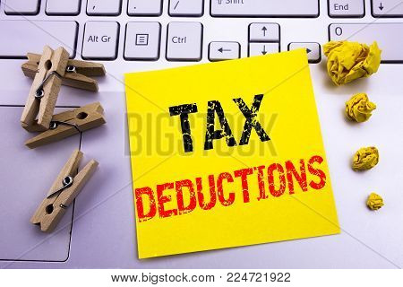 Hand writing text caption inspiration showing Tax Deductions. Business concept for Finance Incoming Tax Money Deduction written on sticky paper on the white keyboard background.