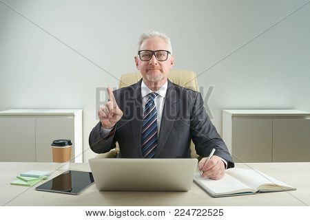 Waist-up portrait of serious aged entrepreneur wearing eyeglasses looking at camera and shaking finger while sitting at office desk and working on important project