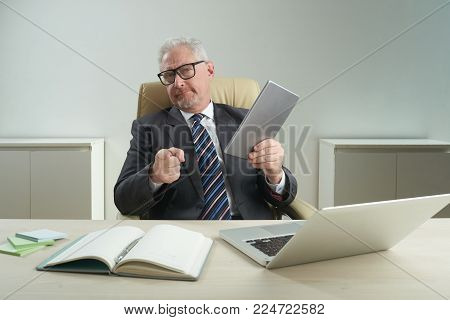 Waist-up portrait of confident senior white collar worker wearing eyeglasses pointing at camera with index finger while holding digital tablet in hand