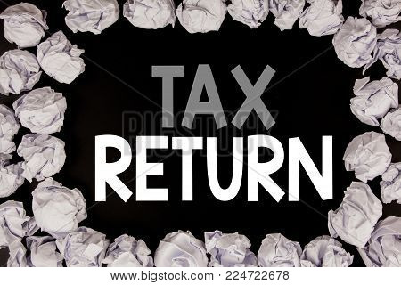Word, writing Tax Return. Business concept for Accounting Money Return written on black background with copy space on background with folded paper balls