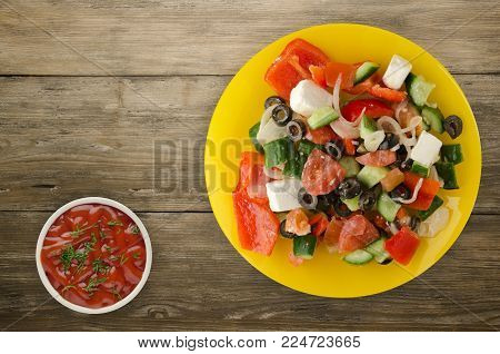 Greek salad on a wooden background . Greek salad on a plate top view . healthy food