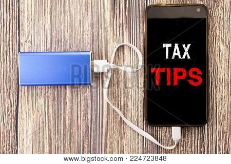 Word, writing Tax Tips. Business concept for Taxpayer Assistance Refund Reimbursement written on mobile phone mobile and power-bank charger on old wood wooden background