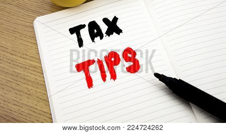 Handwritten text caption showing Tax Tips. Business concept writing for Taxpayer Assistance Refund Reimbursement writte notebook with copy space on book background with marker pen