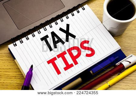 Tax Tips. Business concept for Taxpayer Assistance Refund Reimbursement written on notebook book on wooden background in the Office with laptop coffee