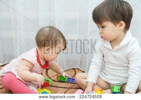 Sisters playing. Two little girls, baby and toddler. jealous child looking with grievance at baby because she break her game