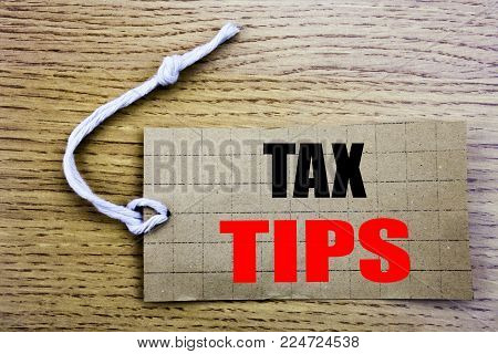 Tax Tips. Business concept for online saleTaxpayer Assistance Refund Reimbursement written on price tag paper with copy space on wooden vintage background