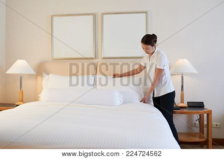 Maid changing linen in hotel room in the morning