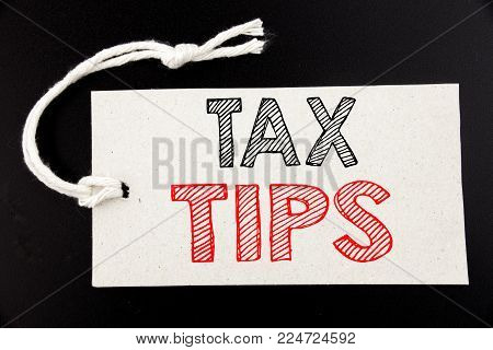 Handwritten text caption showing Tax Tips. Business concept writing for Taxpayer Assistance Refund Reimbursement written on price tag paper on black vintage background.