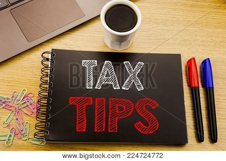 Handwriting Announcement text showing Tax Tips. Business concept for Taxpayer Assistance Refund Reimbursement written on notebook book on wooden background in the Office with laptop coffee