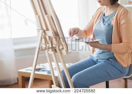 art, creativity and people concept - artist woman with palette knife and easel painting at studio