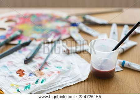 fine art, creativity and artistic tools concept - paintbrush soaking in cup of water and color on paper tissue