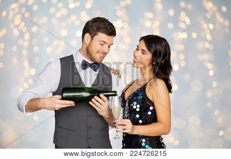 celebration and holidays concept - happy couple with bottle of non alcoholic champagne and wine glass at party over festive lights background