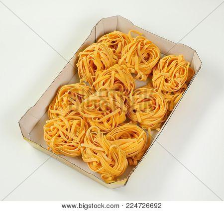 box of dried ribbon pasta bundles on white background