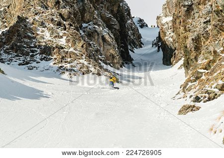 A man a snowboarder freerider descends the backcountry at high speed from a slope leaving behind a trail of snow powder against the backdrop of a rocky couloir. The concept of freeride culture and backcountry destinations in snowboarding