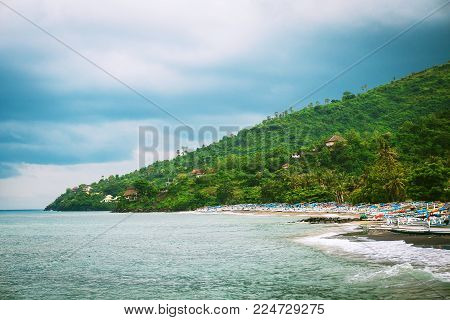 Many fishing boats on the sandy ocean shore in Amed, Bali, Indonesia