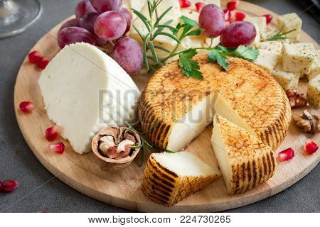 Cheese platter with assorted cheeses, grapes, nuts over gray stone background, copy space. Italian cheese and fruit platter.