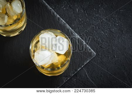 Whiskey on the rocks. Whiskey with ice garnished with citrus twist served on black stone background, top view, copy space.