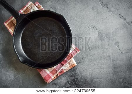 Cast iron pan on rustic grey concrete background close up -  empty black frying pan frying skillet with copy space