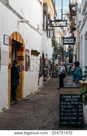 Cordoba, Spain - April 10, 2017: Old typical street in the jewry of Cordoba with restaurants and white walls decorated with flowers
