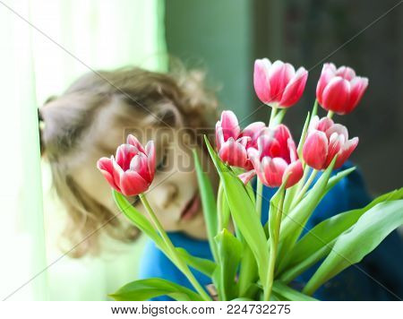 A Little Girl With Bouquet Of Beautiful Spring Tulip Flowers.