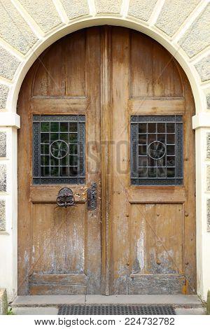 Old vintage brown wooden door with metal bars