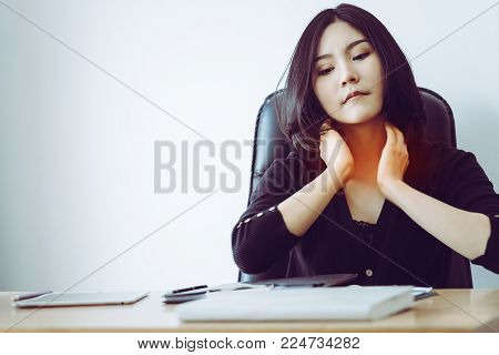 Woman is having sore throat and neck pain in office