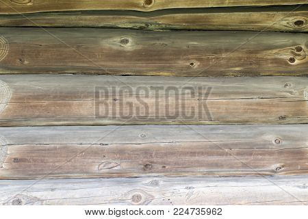 old wooden background of several faded oak logs with twigs, front view