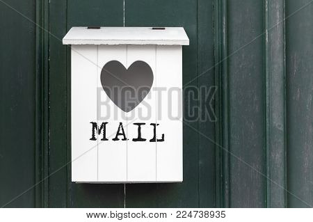 White vintage wooden mailbox with empty heart. In front of the written mail.