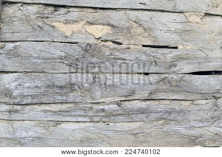 old wooden background of several faded oak boards with wide slits and clay, front view