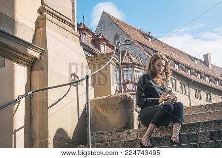 Woman sitting on stairs searching in a purse - Beautiful young woman dressed in black modern clothes, looking in her purse, sitting on stairs in the center of a German town, Schwabisch Hall.