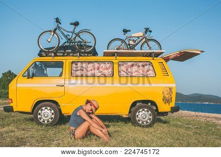 Summer holidays, road trip, vacation, travel and people concept - young hippie women in front of minivan car on beach