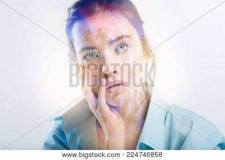 Beautiful deep young girl spending time alone in the bright room touching her face and looking straight.