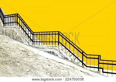 tiled stairs and black steel railing with yellow concrete wall on ramp road