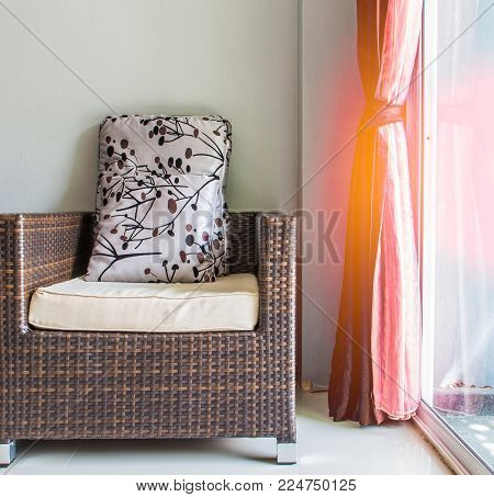 rattan chair near glass door with red blinds