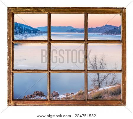 dusk over mountain lake in winter as seen  through vintage, grunge, sash window with dirty glass