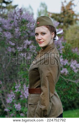 Pretty Soviet female soldier in the form of the Second World war against the background of lilac