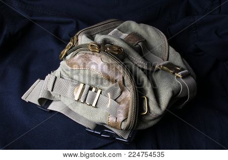 closeup of buckles, clasps, zippers, pockets, fasteners, fittings and seams on the hand bag of coarse cotton fabric
