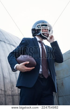 low angle view of young businessman in suit and rugby helmet holding ball in hands on street