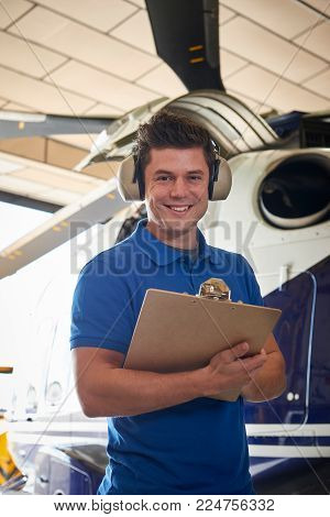 Portrait Of Male Aero Engineer With Clipboard Carrying Out Check On Helicopter In Hangar