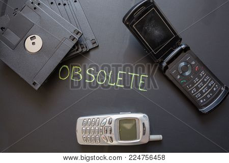 Old mobile phones and floppy disks on dark background. Obsolete electronic equipment.